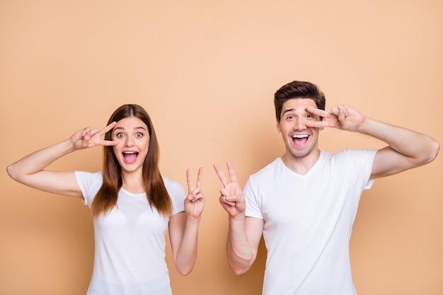 Porträt von ihm er sie sie schönes attraktives reizendes funky überglückliches fröhliches fröhliches paarteam, das weißes t-shirt trägt, das v-zeichen zeigt, das über beigem pastellfarbenem hintergrund lokalisiert wird