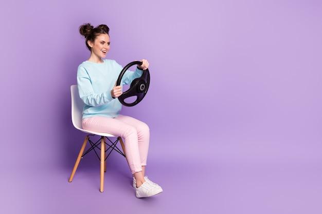 Porträt von ihr hübsch aussehendes, attraktives, fröhliches, fröhliches mädchen, das auf einem stuhl sitzt und das lenkrad in den händen hält und vorgibt, auto zu fahren, isoliert auf violett-violettem, pastellfarbenem hintergrund