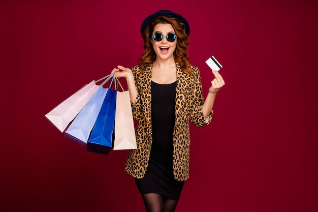 Porträt von ihr hübsch aussehendes attraktives hübsches reiches fröhliches fröhliches, gewelltes mädchen, das in den händen bankkartentaschen hält konsumismus einzeln auf rotem kastanienbraunem burgunder-marsala-farbhintergrund