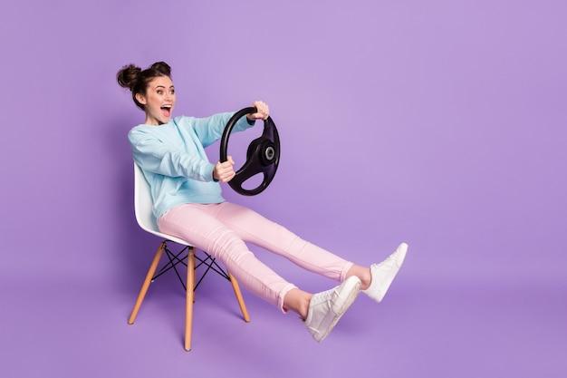 Porträt von ihr hübsch aussehendes, attraktives, lustiges, fröhliches, fröhliches mädchen, das auf einem stuhl sitzt und das lenkrad in den händen hält, wie ein auto, isoliert auf violettem lila lila pastellfarbenem hintergrund