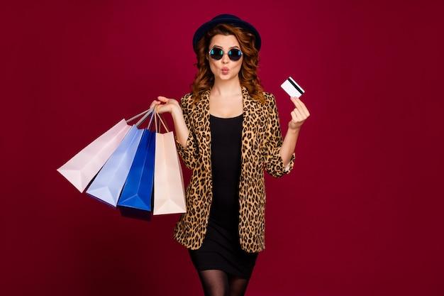 Porträt von ihr hübsch aussehendes, hübsches, reiches, fröhliches, gewelltes mädchen, das in den händen hält bankkarte neue kleidung schmollen lippen einzeln auf rotem kastanienbraunem burgunder-marsala-farbhintergrund