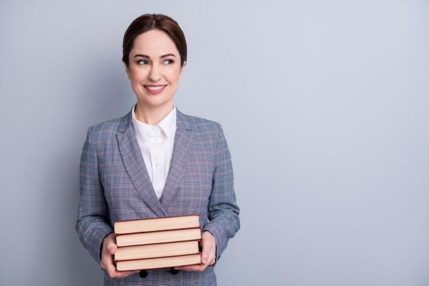 Porträt von ihr, sie hübsche attraktive hübsche qualifizierte kluge, fröhliche bibliothekarin, die einen lässigen karierten blazer trägt, der buchkopienraum isoliert grauer pastellfarbener hintergrund hält