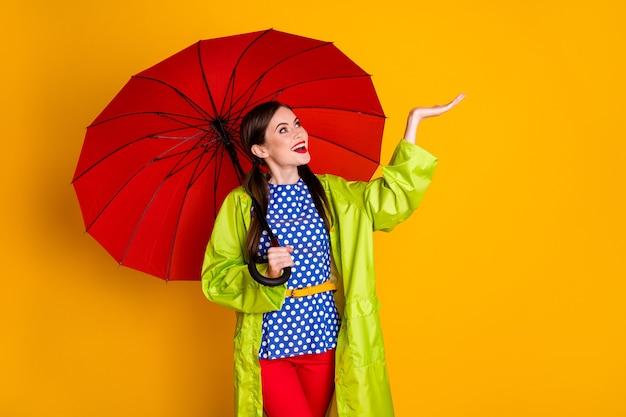 Porträt von ihr, sie ist ein hübsches, attraktives, fröhliches, fröhliches, modisches mädchen, das einen grünen regenmantel trägt, der regentropfen auf der handfläche hält, isoliert hell leuchtender, leuchtend gelber farbhintergrund