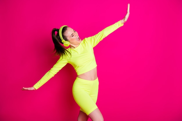 Porträt von ihr, sie ist ein hübsches, attraktives, sorgloses, fröhliches mädchen, das popmusik hört und das tanzen genießt und spaß hat gute laune isoliert heller, lebendiger glanz, lebendiger rosafarbener, fuchsiafarbener hintergrund