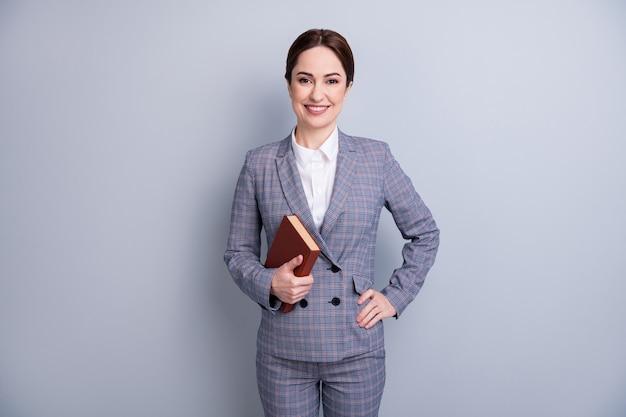 Porträt von ihr, sie ist ein netter attraktiver, fachkundiger, fröhlicher tutor, der einen lässigen karierten anzug trägt, der akademisches buchwissen am 1. september einzeln auf grauem pastellfarbenem hintergrund hält