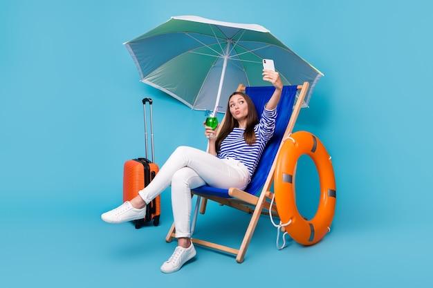Porträt von ihr, sie ist ein schönes, attraktives, funky fröhliches mädchen, das auf einem stuhl unter einem sonnenschirm sitzt und exotischen mojito trinkt, der ein selfie macht, das luftkuss sendet, isoliert hell leuchtender, lebendiger blauer farbhintergrund