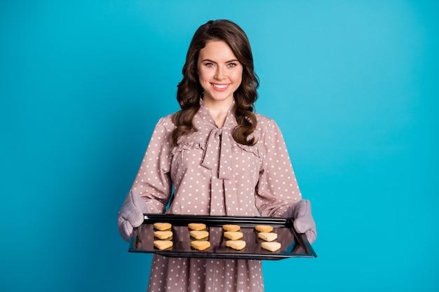 Porträt von ihr, sie ist eine schöne, attraktive, hübsche, fröhliche, gewellte freundin, die in der hand hält tablett mit frischen, heißen, leckeren keksen einzeln auf hell leuchtendem, leuchtend blauem hintergrund