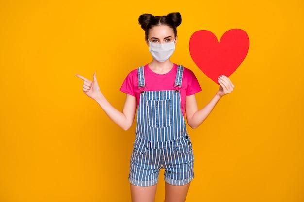 Porträt von ihr, sie nettes mädchen, das in der hand papierherz hält und eine sicherheitsmaske trägt, die den kopienraum medizinleben krankenversicherung zeigt, isoliert hell leuchtend leuchtend gelber farbhintergrund