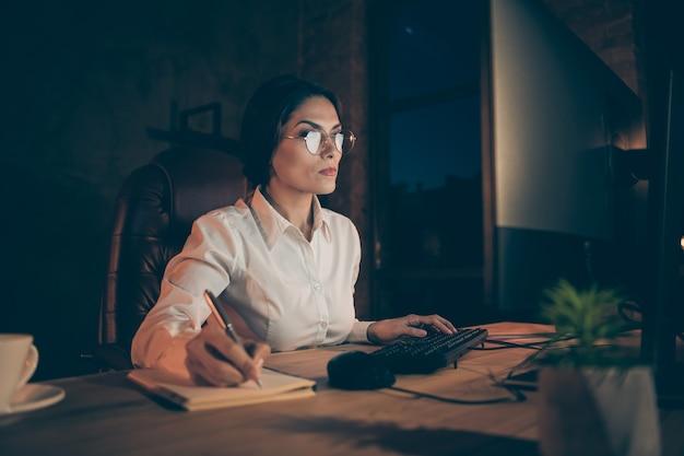 Porträt von ihr sie schön attraktiv schön stilvoll klug klug intelligent intelligent erfahrene dame hai experte spezialist schreiben notizen startup in der nacht dunklen arbeitsplatz station drinnen