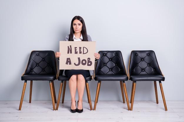 Porträt von ihr, sie schöne attraktive arme elende depressiv gefeuerte büroleiterin, die auf einem stuhl sitzt und ein poster hält, das jobkostensenkung sucht, isolierter pastellgrauer farbhintergrund