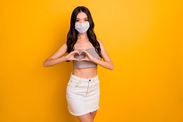 Porträt von ihr sie schöne attraktive brünette freundin zeigt herzform schild mit sicherheitsgaze maske stop mers cov kontamination isoliert heller, lebendiger glanz, leuchtend gelber farbhintergrund