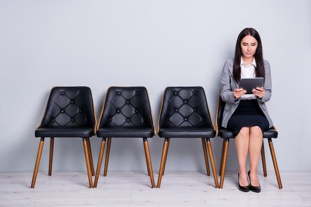 Porträt von ihr, sie schöne attraktive, edel fokussierte, selbstbewusste vermarkterin, die auf einem stuhl sitzt und e-book-gadget-index-investitions-anti-krisen-plan liest, isoliert pastellgrauer farbhintergrund