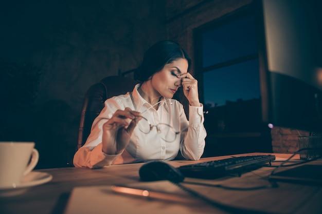 Porträt von ihr sie schöne attraktive erschöpfte wirtschaftswissenschaftlerin wirtschaftsprüferin rechtsanwältin top-managerin, die schwierige aufgabenfrist in der nacht dunkle arbeitsstation drinnen erfüllt