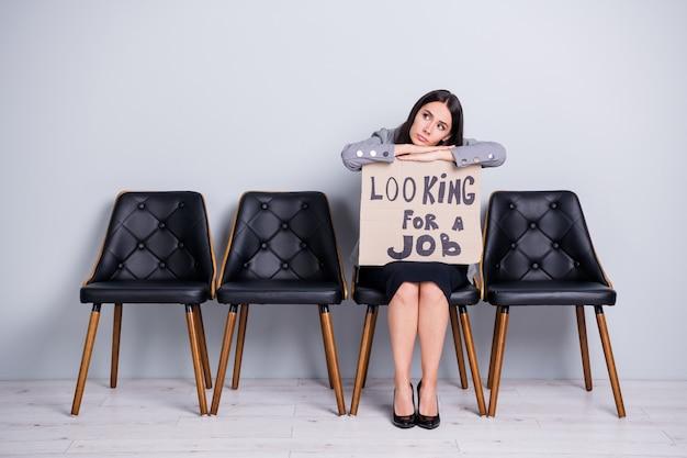 Porträt von ihr, sie schöne, attraktive, langweilige, elende büroleiterin, die auf einem stuhl sitzt und ein promo-poster hält, der nach job sucht, isolierter pastellgrauer farbhintergrund