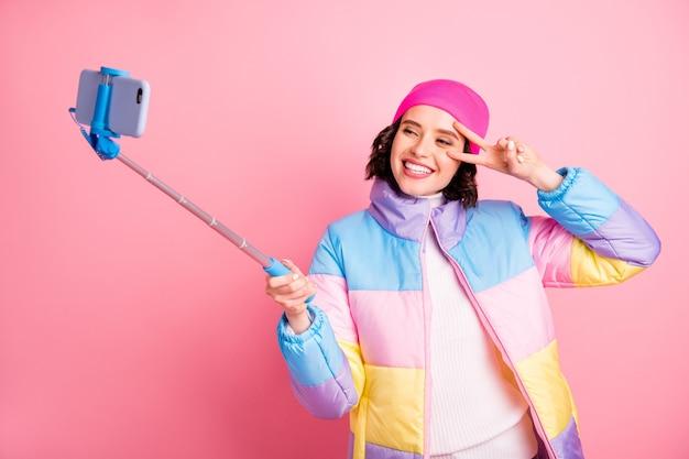 Porträt von ihr sie schöne attraktive schöne fröhliche fröhliche freundin, die selfie macht, das v-zeichen-party-freizeitblog-blogger zeigt, der über rosa pastellhintergrund isoliert wird