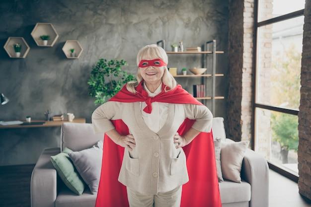 Porträt von ihr sie schöne attraktive starke starke kraftvolle fröhliche fröhliche fröhliche grauhaarige dame, die rote kostüm-super-oma am modernen innenhaus des industriellen backsteinlofts trägt