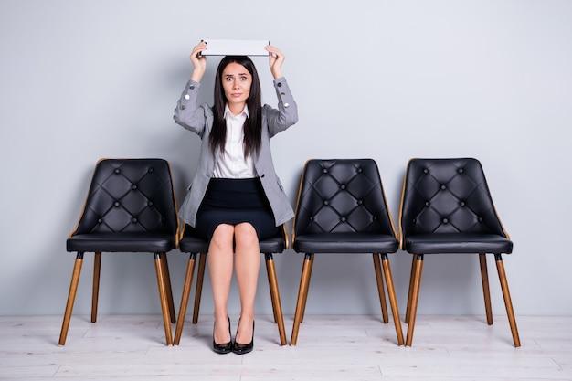 Porträt von ihr, sie schöne, attraktive, verängstigte managerin, die auf einem stuhl sitzt und ein dokument über dem kopf hält, wie eine dachversicherung, auf ein treffen mit isoliertem pastellgrauen farbhintergrund
