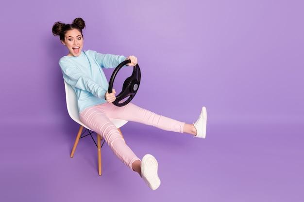 Porträt von ihr, sie schönes attraktives fröhliches mädchen, das auf einem stuhl sitzt und das lenkrad in der hand hält, wie das fahren eines unsichtbaren autotransportfahrzeugs isoliert violett lila lila pastellfarben
