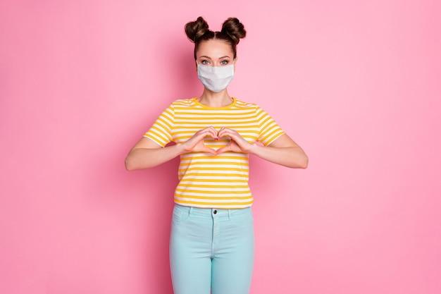 Porträt von ihr, sie schönes attraktives gesundes mädchen mit sicherheitsmaske mit herzformzeichen pandemie-krankheit mers cov herzkardiologie risikomedizin isoliert pastellrosa farbhintergrund