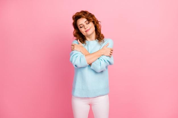 Porträt von ihr, sie sieht gut aus, attraktiv, hübsch, hübsch, fröhlich, fröhlich, verträumt, wellenhaariges mädchen, das sich einzeln auf rosafarbenem pastellfarbenem hintergrund in den urlaub umarmt