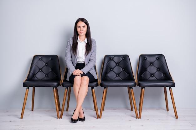 Porträt von ihr, sie sieht gut aus, attraktive, hübsche, elegante dame, anwältin, anwältin, die auf dem stuhl sitzt und erwartet, die personalabteilung zu treffen, isoliert heller pastellgrauer farbhintergrund