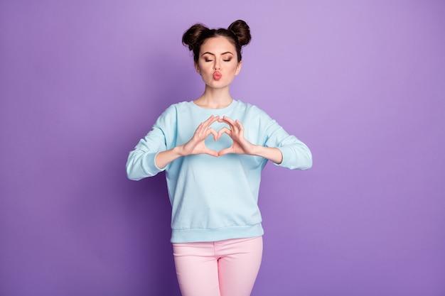 Porträt von ihr, sie sieht gut aus, attraktives, hübsches, verträumtes, amouröses mädchen, das ein herzsymbol zeigt, das luftkuss einzeln über violett-violetter, heller, lebendiger, leuchtender farbhintergrund sendet