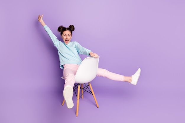 Porträt von ihr, sie sieht hübsch aus, attraktiv, charmant, kindisch, komisch, ekstatisch, fröhliches, fröhliches mädchen, das auf stuhlreiten sitzt und spaß hat, isoliert auf violett-violettem, pastellfarbenem hintergrund