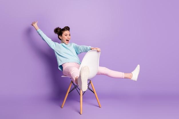Porträt von ihr, sie sieht hübsch aus, attraktiv, kindisch, komisch, verspielt, fröhlich, fröhliches mädchen, das auf stuhlreiten sitzt und spaß hat, gute laune zu täuschen, einzeln auf violett-violettem, pastellfarbenem hintergrund