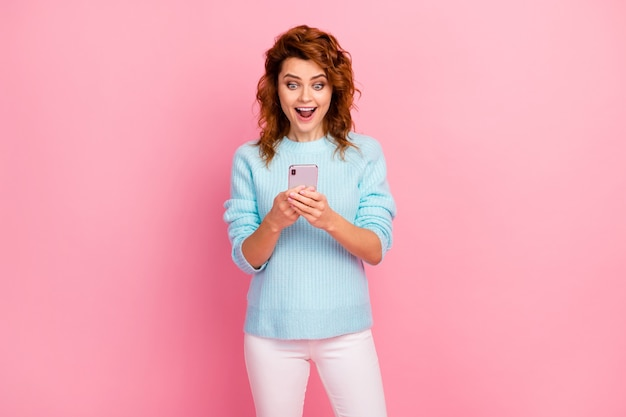 Porträt von ihr, sie sieht hübsch aus, hübsch hübsch, ziemlich froh, süchtig, fröhlich, fröhlich, gewelltes mädchen, das sms-gehaltsbenachrichtigungen verwendet, die auf rosafarbenem pastellfarbenhintergrund isoliert sind