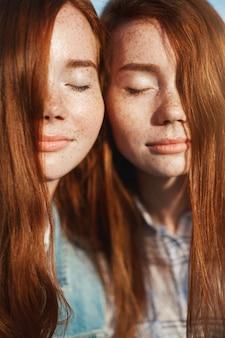 Porträt von ingwer-zwillingsschwestern mit geschlossenen augen. ihre schwesternschaft und freundschaft genießen. ältere und jüngere schwester leben glücklich.