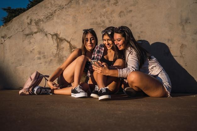 Porträt von jugendlichen freunden, die sitzen und ein smarthphone in einem stadtpark betrachten