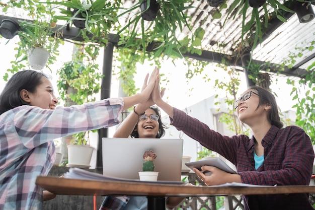 Porträt von jungen asiatischen studenten, die sich in einem café treffen, das zusammen high five macht