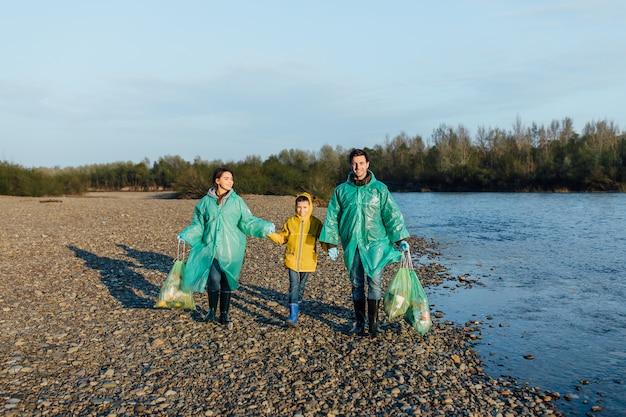 Porträt von jungen freiwilligen und kindern, die müll im see bin im park sammeln. ökologiegruppe. konzept des umweltschutzes.