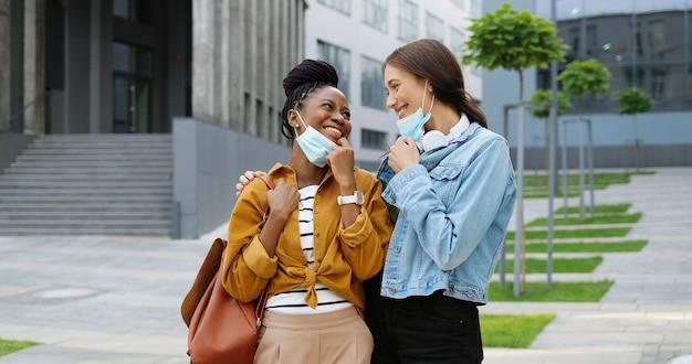 Porträt von jungen fröhlichen weiblichen besten freunden gemischter rassen, die medizinische masken auf der straße abnehmen und lächeln. multiethnische glückliche studentinnen im freien. afroamerikanerinnen und kaukasische frauen. pandemie.