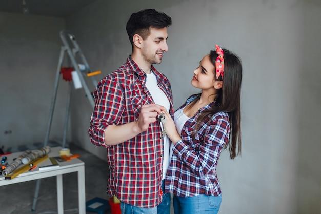 Porträt von jungen glücklichen zufälligen paaren, einen schlüssel halten, kaufte die neue wohnung für familie und tat reparatur zusammen