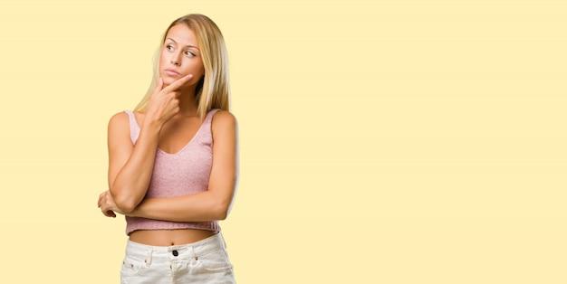 Porträt von jungen hübschen blondinen, die oben denken und schauen, verwirrt über eine idee