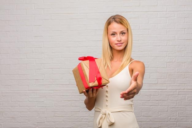 Porträt von jungen hübschen blondinen gegen eine ziegelsteinwand, die heraus erreicht, um jemanden zu grüßen