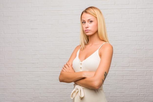 Porträt von jungen hübschen blondinen gegen eine ziegelsteinwand, die seine arme kreuzt, ernst und
