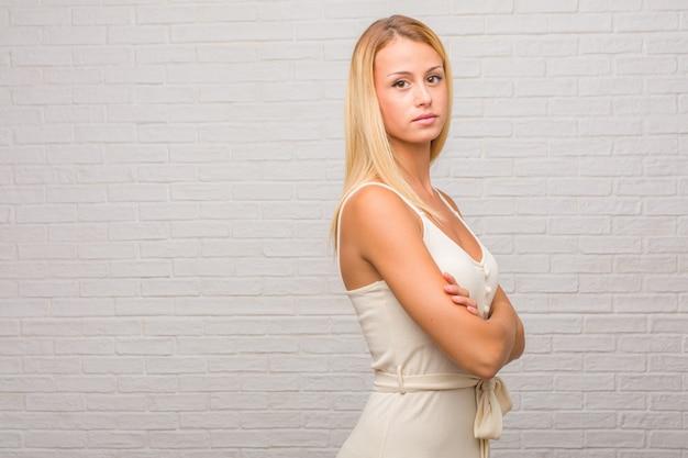 Porträt von jungen hübschen blondinen gegen eine ziegelsteinwand, die seine arme kreuzt, lächelt und glücklich und überzeugt und freundlich ist