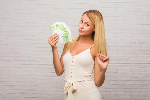 Porträt von jungen hübschen blondinen gegen eine ziegelsteinwand hörend musik, tanzend und spaß habend, bewegen, schreien und glück, freiheitskonzept ausdrücken. halten von euro-banknoten.