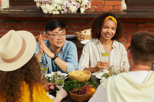 Porträt von jungen leuten, die abendessen mit freunden im freien genießen und erfrischende cocktails halten, während sie während der sommerparty am tisch sitzen