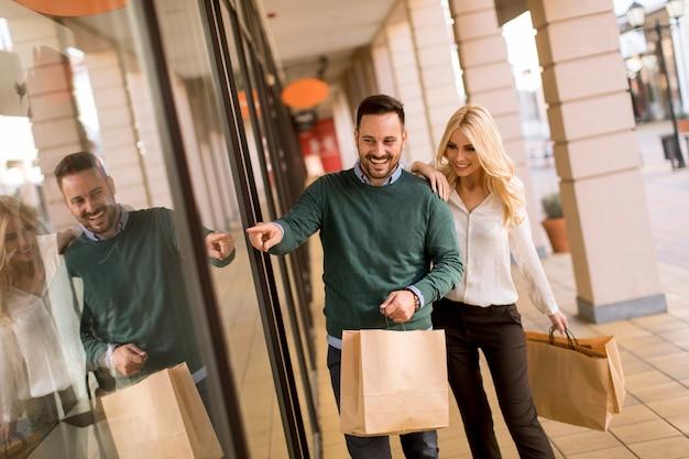 Porträt von jungen paaren mit einkaufstaschen in der stadt