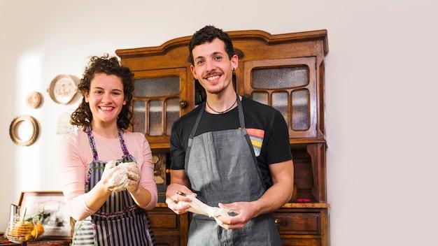 Porträt von jungen paaren mit geknetetem teig in ihren händen