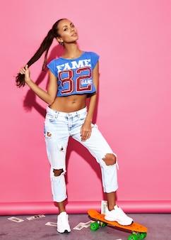 Porträt von jungen sexy stilvollen brunettefrauen mit pennyskateboard. modellieren sie in der heißen sporthippie-kleidung des sommers, die nahe rosa wand aufwirft.