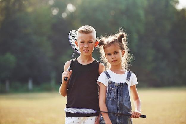 Porträt von jungen und mädchen, die am sonnigen tag mit tennisschlägern in den händen auf dem feld stehen.
