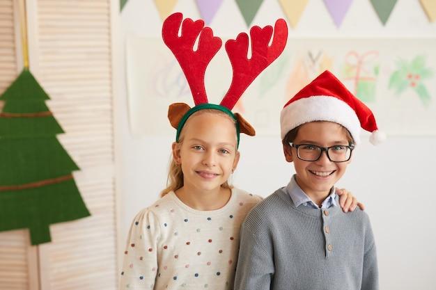 Porträt von jungen und mädchen, die weihnachtsmützen tragen und kamera betrachten, während klasse an weihnachten genießen, raum kopieren