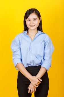 Porträt von jungen und süßen chinesen im japanischen stil posieren für die kamera mit positiver geste und freundlichem lächeln auf gelber kamera.