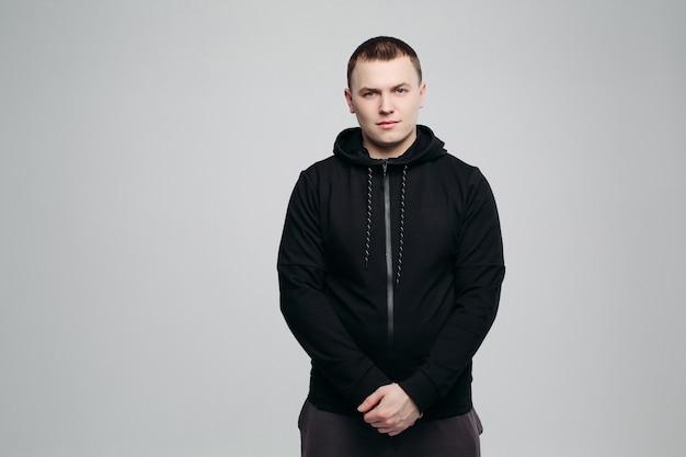 Porträt von jungen und von gutaussehendem mann im schwarzen hoodie