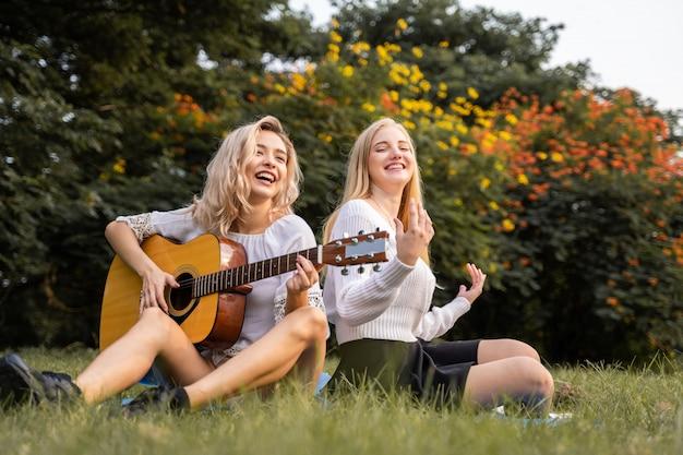 Porträt von kaukasischen jungen frauen, die im park draußen sitzen und eine gitarre spielen, singen ein lied zusammen mit glück
