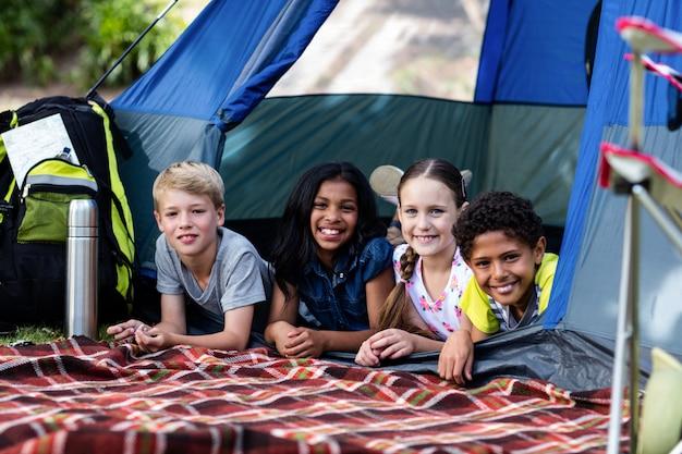 Porträt von kindern, die in einem zelt liegen